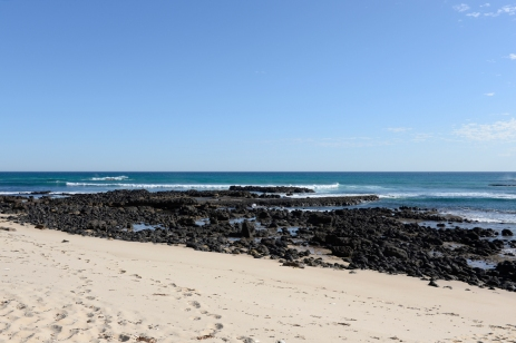 Une plage de sable fin et ses roches volcaniques noires.