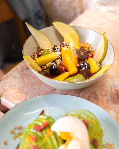 Du bon granola maison servi avec un coulis de fruits et des fruits frais.