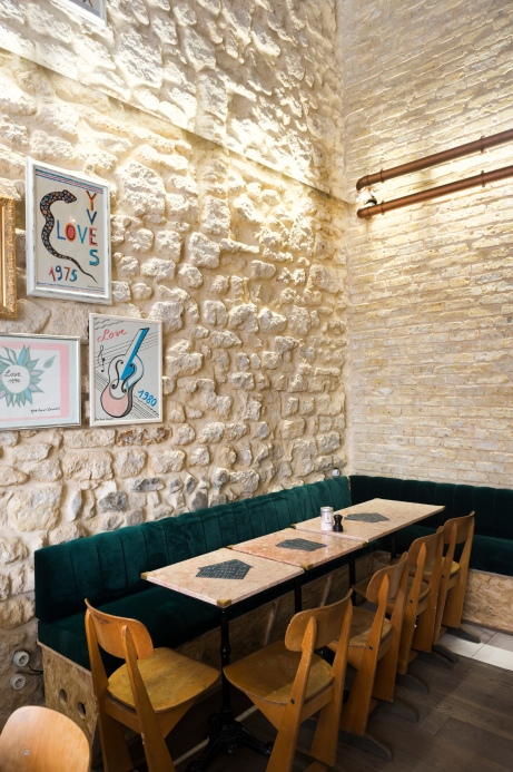 La jolie décoration de chez Café Foufou avec ses miroirs au plafond, ses vieilles pierres au mur et ses tables en marbre rose.