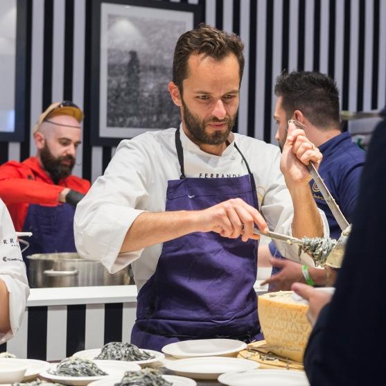 Yoni Saada aide la brigade de Denny Imbroisi pour le service des Tagliolini frais au charbon végétal, artichauts et citrons d'Amalfi, servis dans la meule de Grana Padano.
