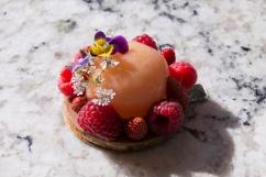 Sablé fruits secs, panacotta au miel, pêche blanche pochée à la lavande, fraises des bois, framboises, fleurs comestibles.