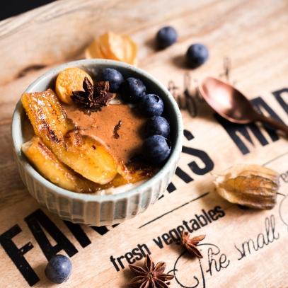 Porridge aux flocons d'avoine et de quinoa, banane poêlée, bleuets, physalis et épices douces.