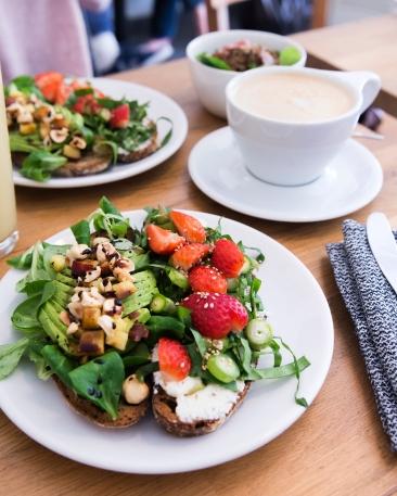 Tartines, petites salades et latté. Tartine fraises asperges et fromage frais à droite, tartine avocat pêches et noisettes à gauche.