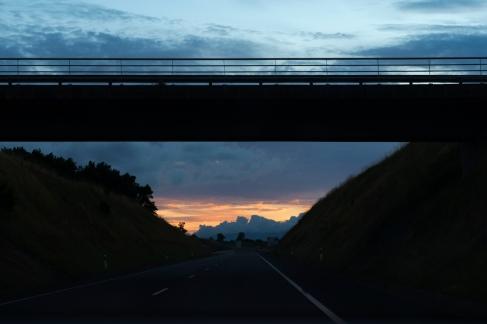 Au loin, le ciel se teinte d'orange et de nuages bleutés.