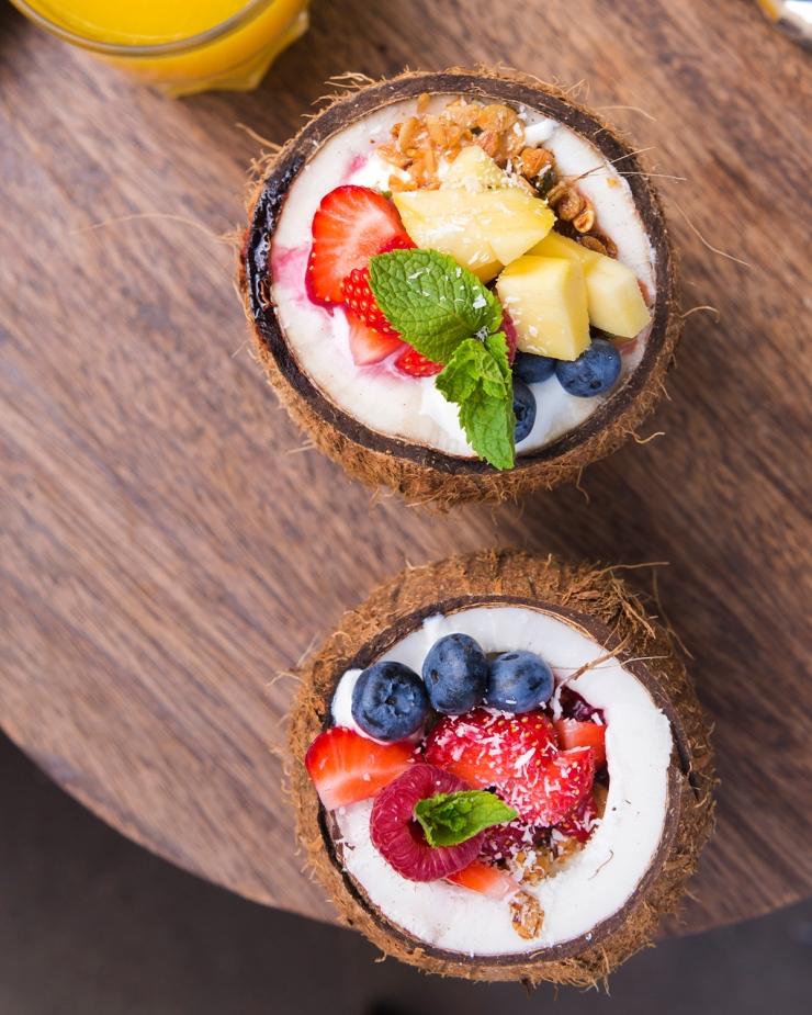 Photo du dessus de deux noix de coco remplies de granola.