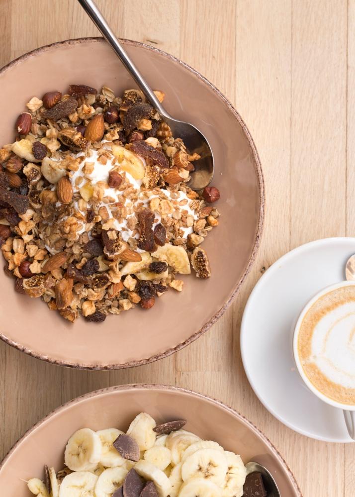 Photo du dessus d'un petit déjeuner dans un café parisien avec 2 assiettes de granola et un café.