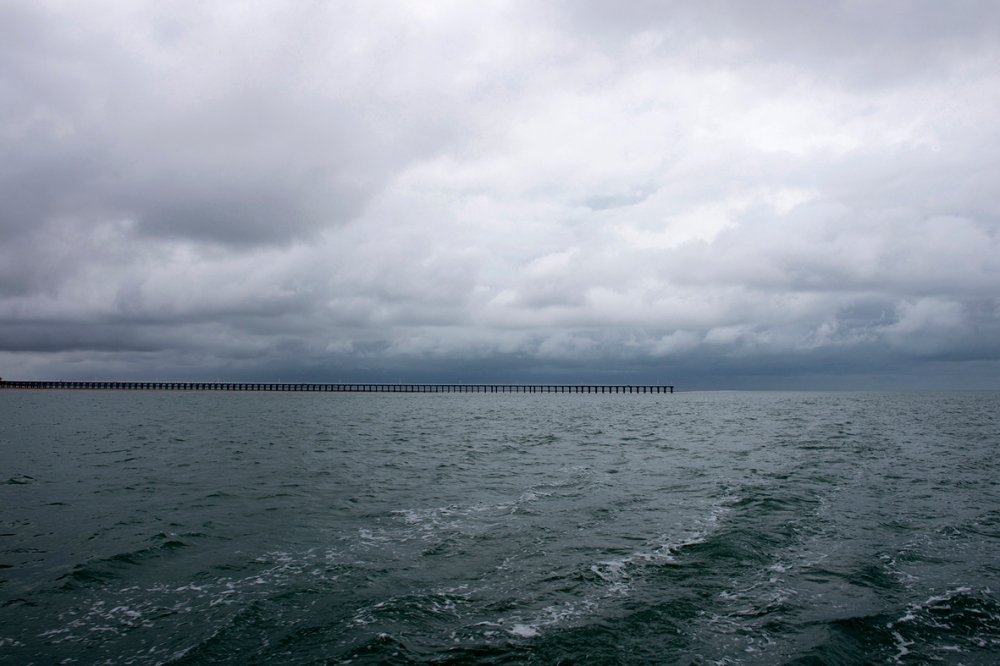 Photographie d'une jetée sur la mer, ciel nuageux.