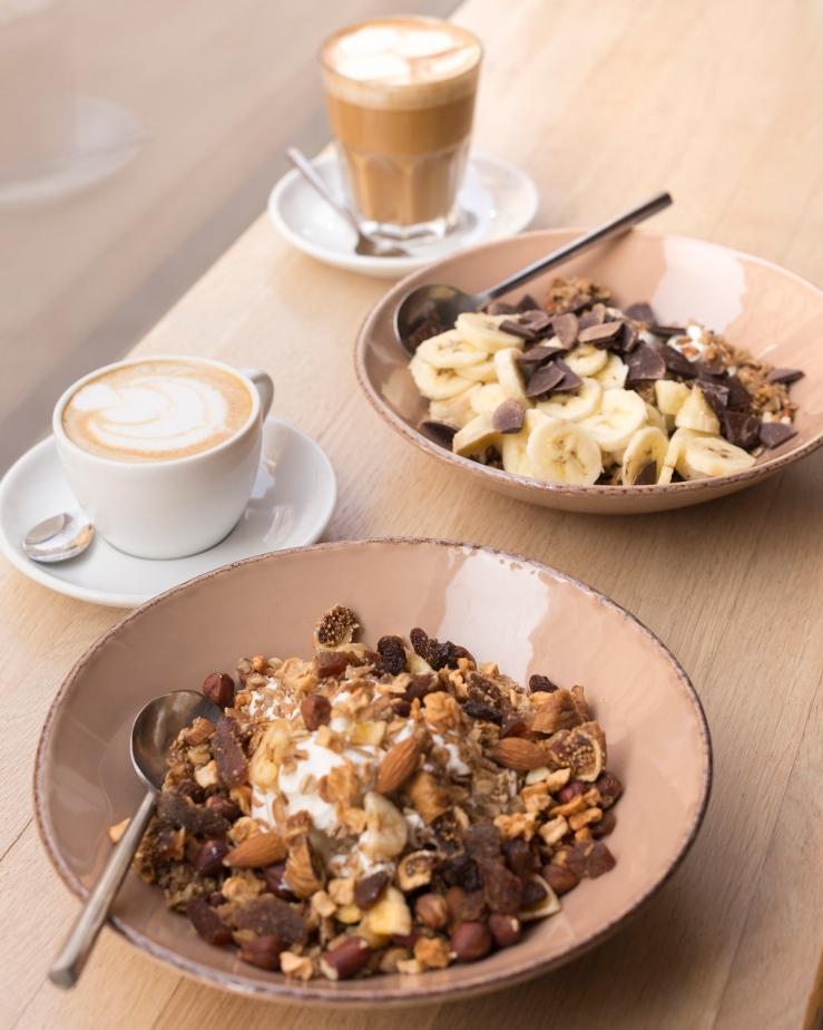 Photo de face de 2 assiettes de granolas et 2 boissons chaudes.