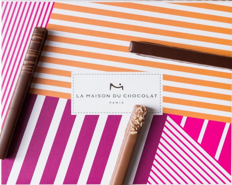 Photographie du dessus de petites barres de chocolat sur une boîte colorée.