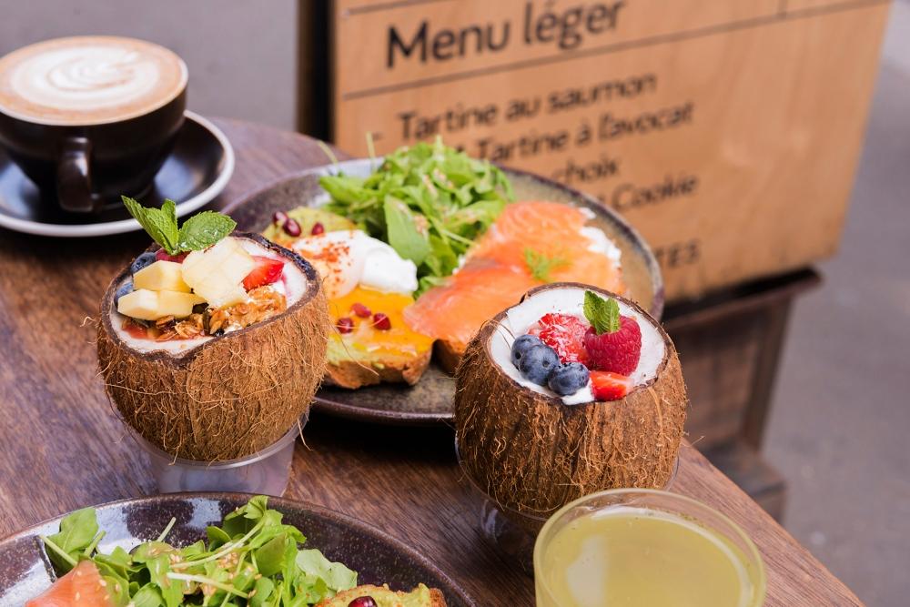 Photo du brunch dans un café parisien avec des noix de coco remplies de granola.