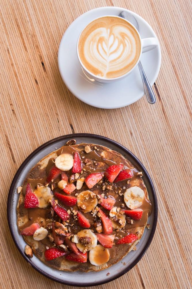 Photo du dessus d'un pancake recouvert de fruits et d'un cappuccino.
