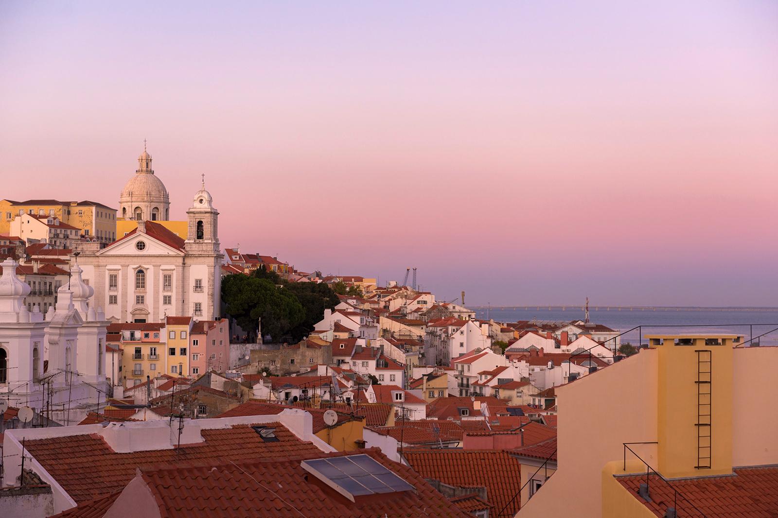 Photo d'un ciel rose sur la vieille ville de Lisbonne.