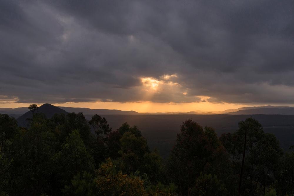 Photographie d'un paysage avec un ciel jaune et des nuages gris