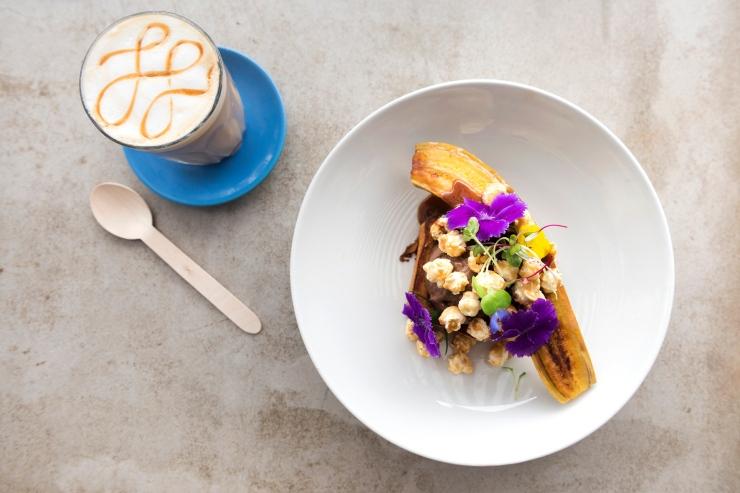 Photographie du dessus d'un dessert avec une banane poêlée et d'un café au lait.