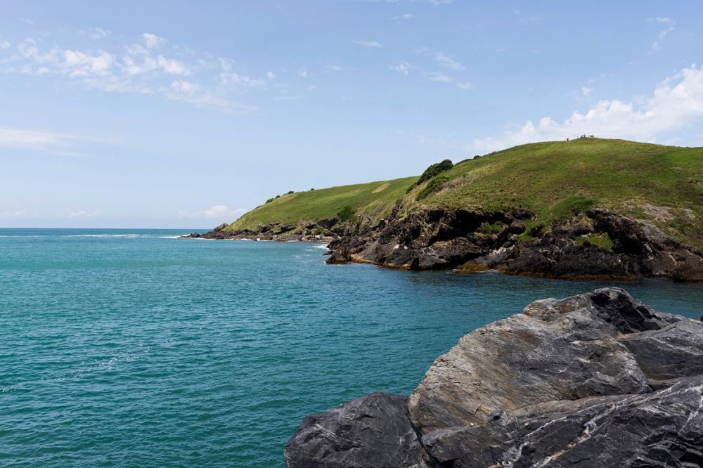 Photographie d'une plaine verdoyante sur la mer.