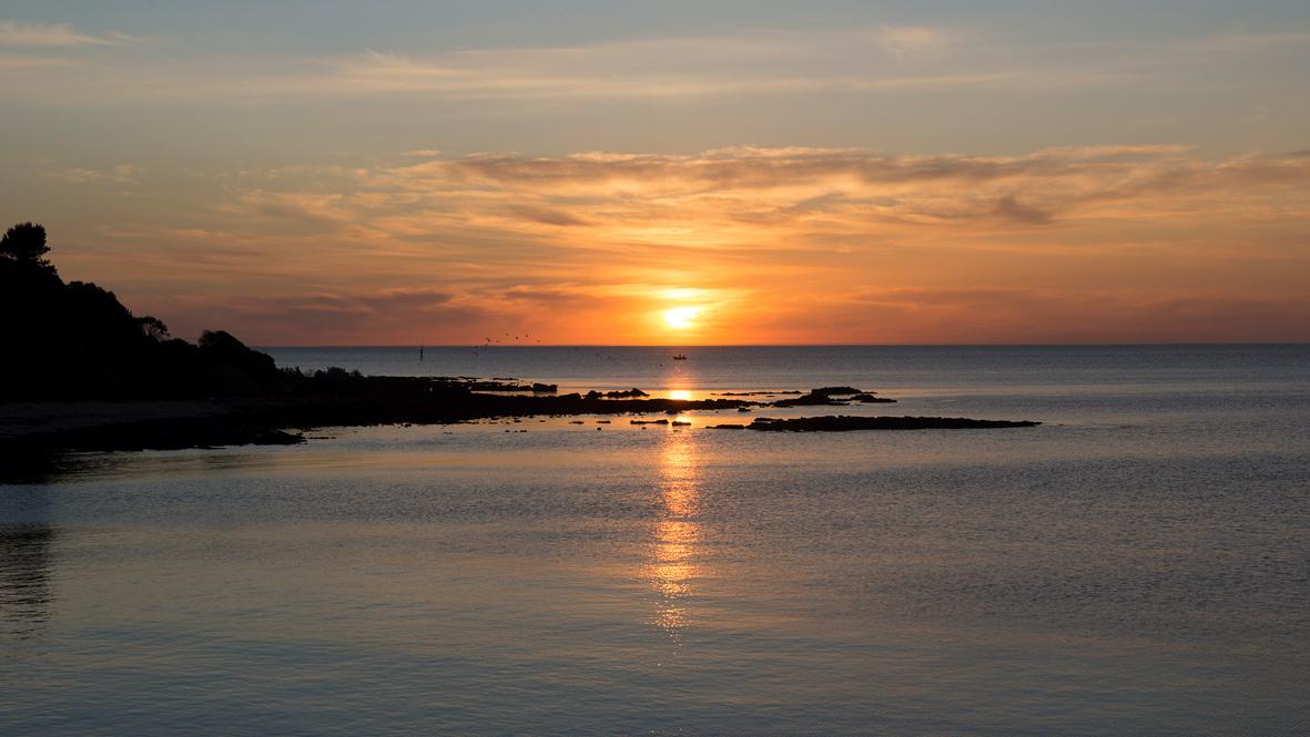 Photographie d'un coucher de soleil sur la mer.