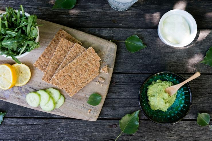 Photographie du dessus d'une table apéro avec crackers et guacamole.