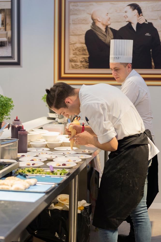Photo de cuisiniers en train de dresser les assiettes au festival Taste of Paris.