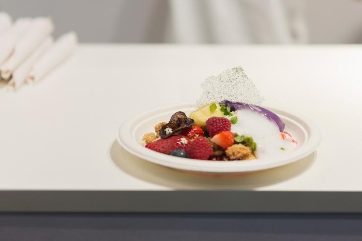 Photographie d'un dessert sur un passe plat, prêt à être envoyé.