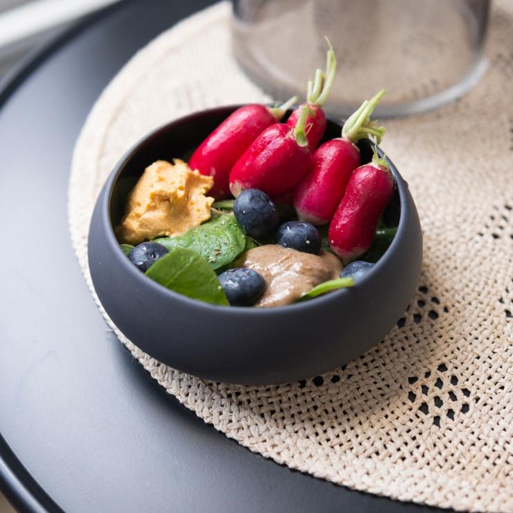 Photo de face d'un bol avec des radis et des bleuets.