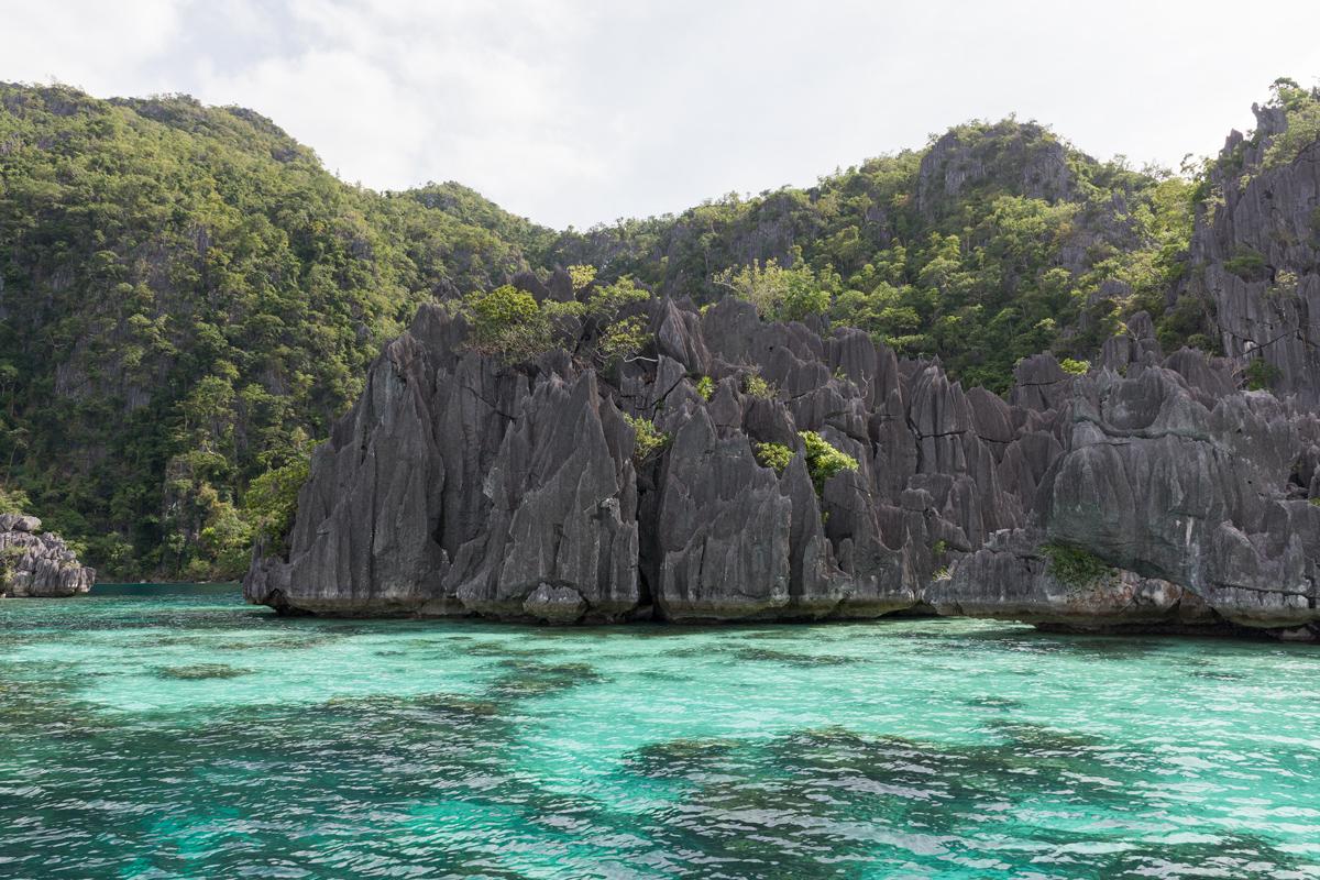 Photographie de roches noires sur la mer turquoise.