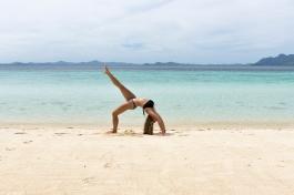 La posture du pont avec une jambe tendue, à la plage aux Philippines.