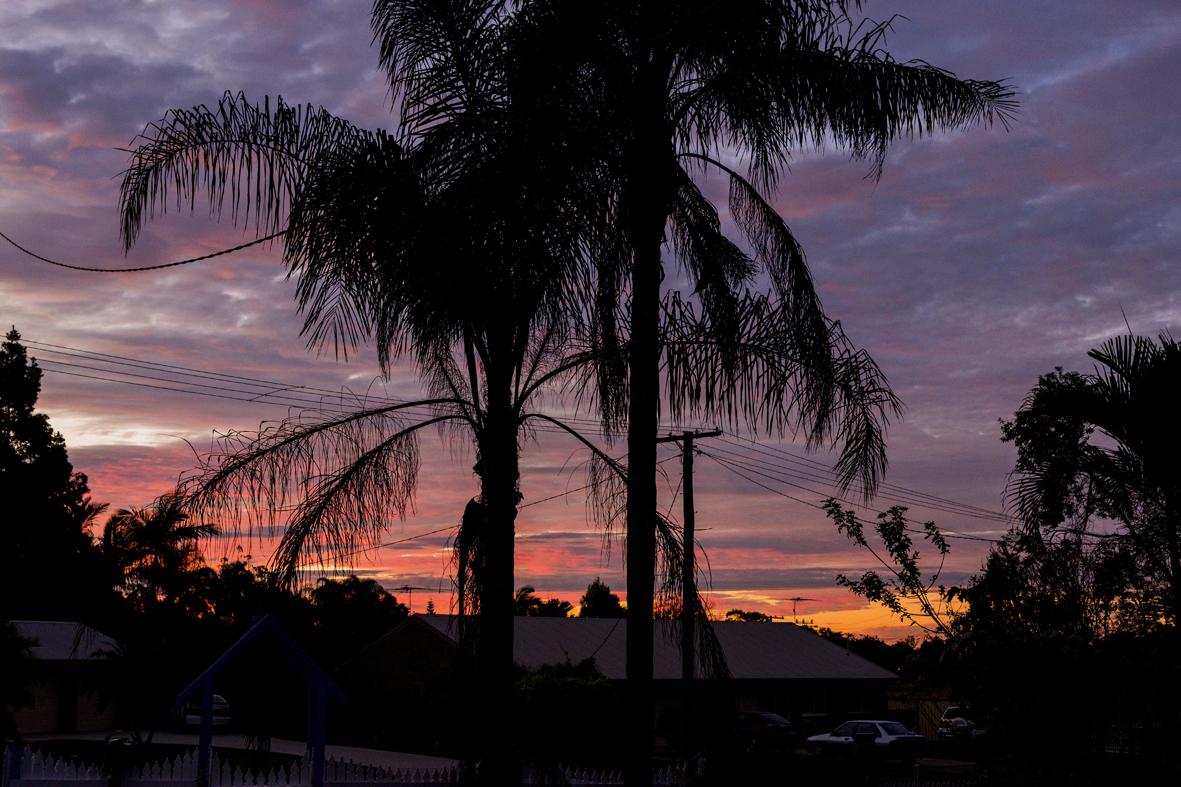 Photographie d'un coucher de soleil qui donne des teintes roses, violettes et oranges au ciel.
