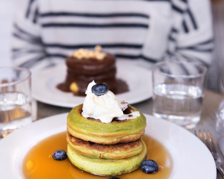 Photo de face d'une pile de 2 pancakes vert avec mascarpone au chocolat blanc sur le dessus.