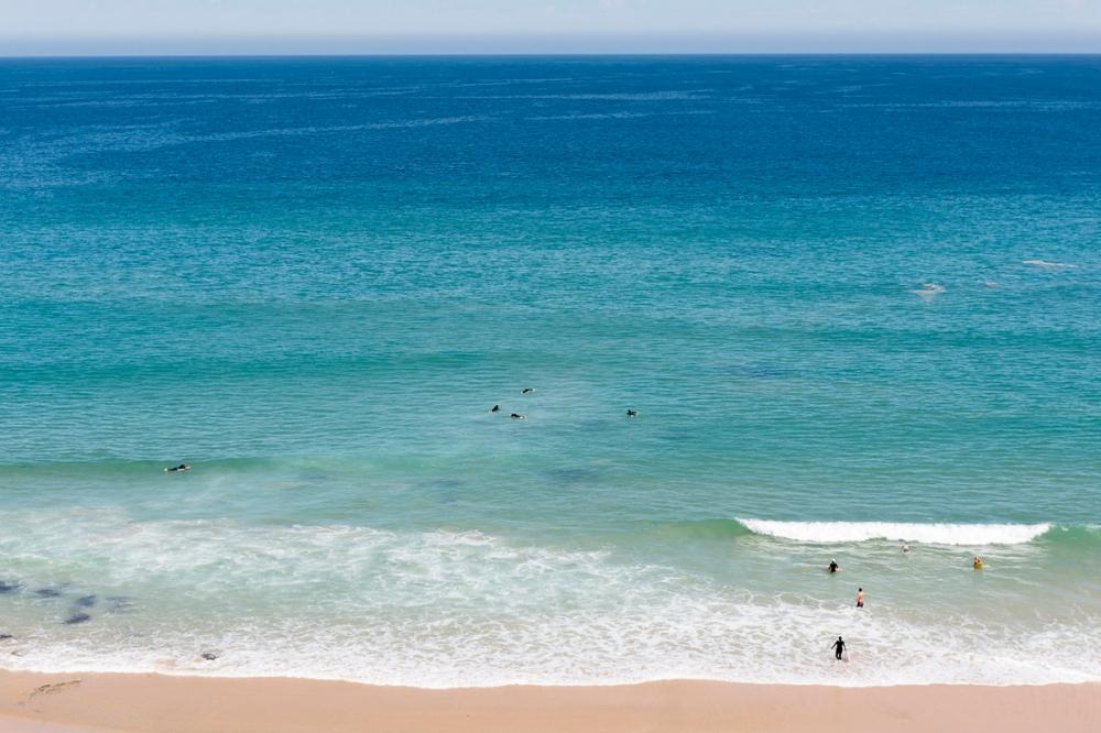 Photographie de l'océan avec des surfeurs.