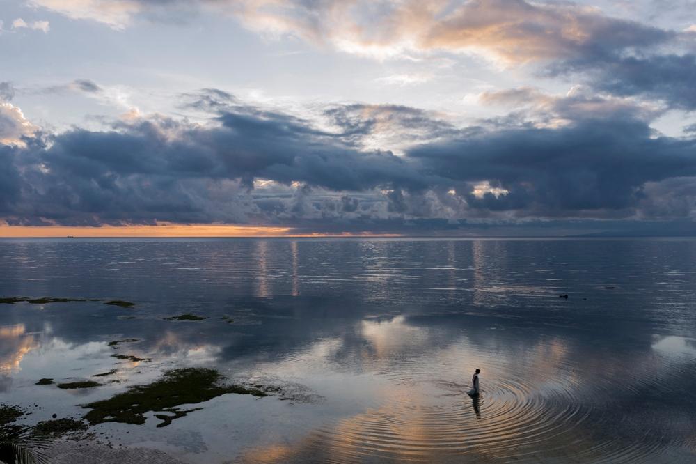 Photographie d'une pêcheuse marchant dans l'eau.