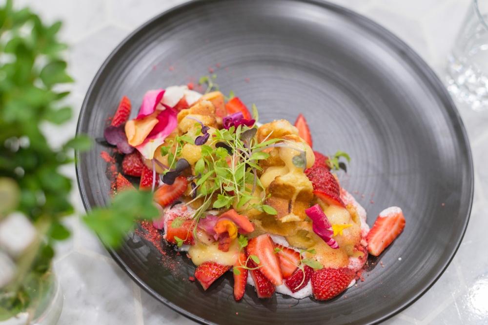 Photographie du dessus d'un dessert à l'assiette aves des gaufres et des fruits rouges.