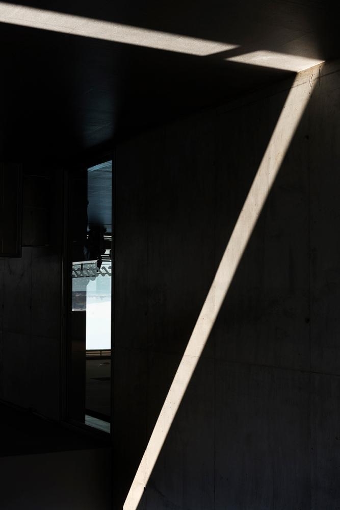 Photographie d'un rayon de lumière diffracté dans un bâtiment de Lisbonne, dessinant un triangle.