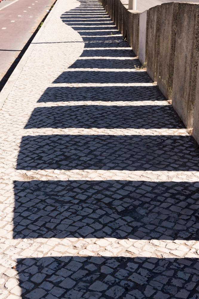 Photographie d'ombres au sol dans les rues de Lisbonne.
