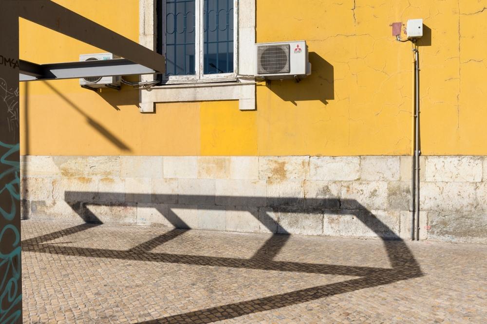 Photographie de face d'une façade avec l'ombre d'un abri de bus à Lisbonne.