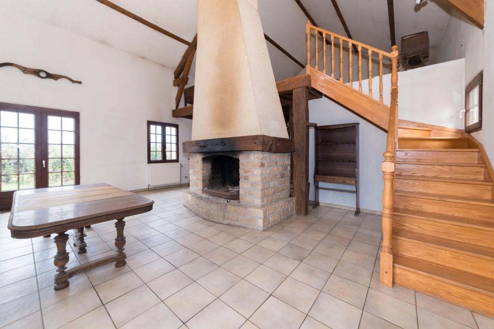 Photographie de l'intérieur d'une habitation avec cheminée centrale.