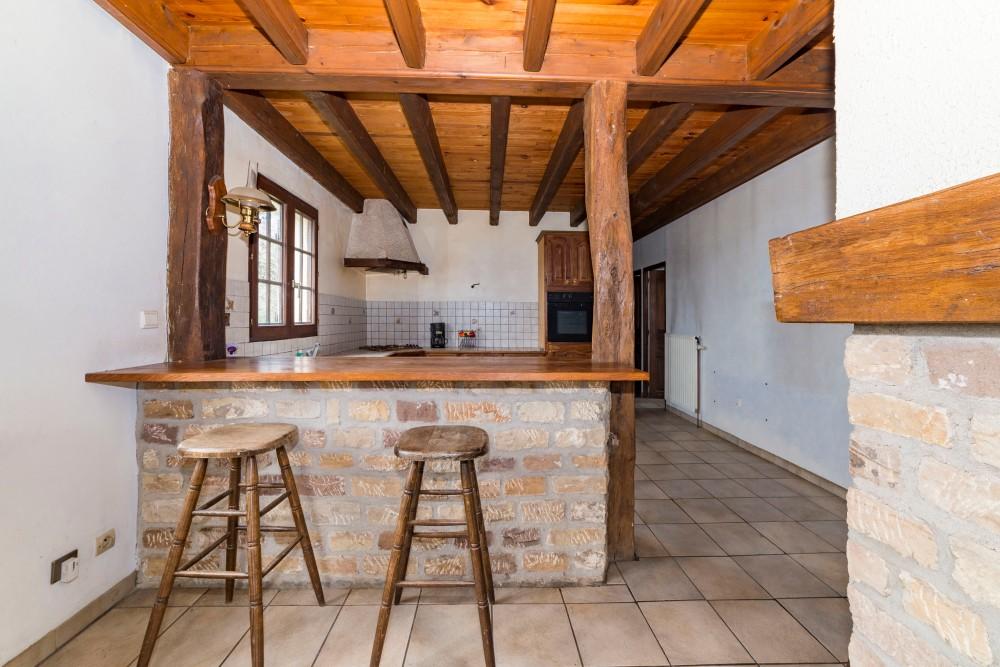 Photographie d'une cuisine rustique avec bar en pierres et en bois dans une habitation.