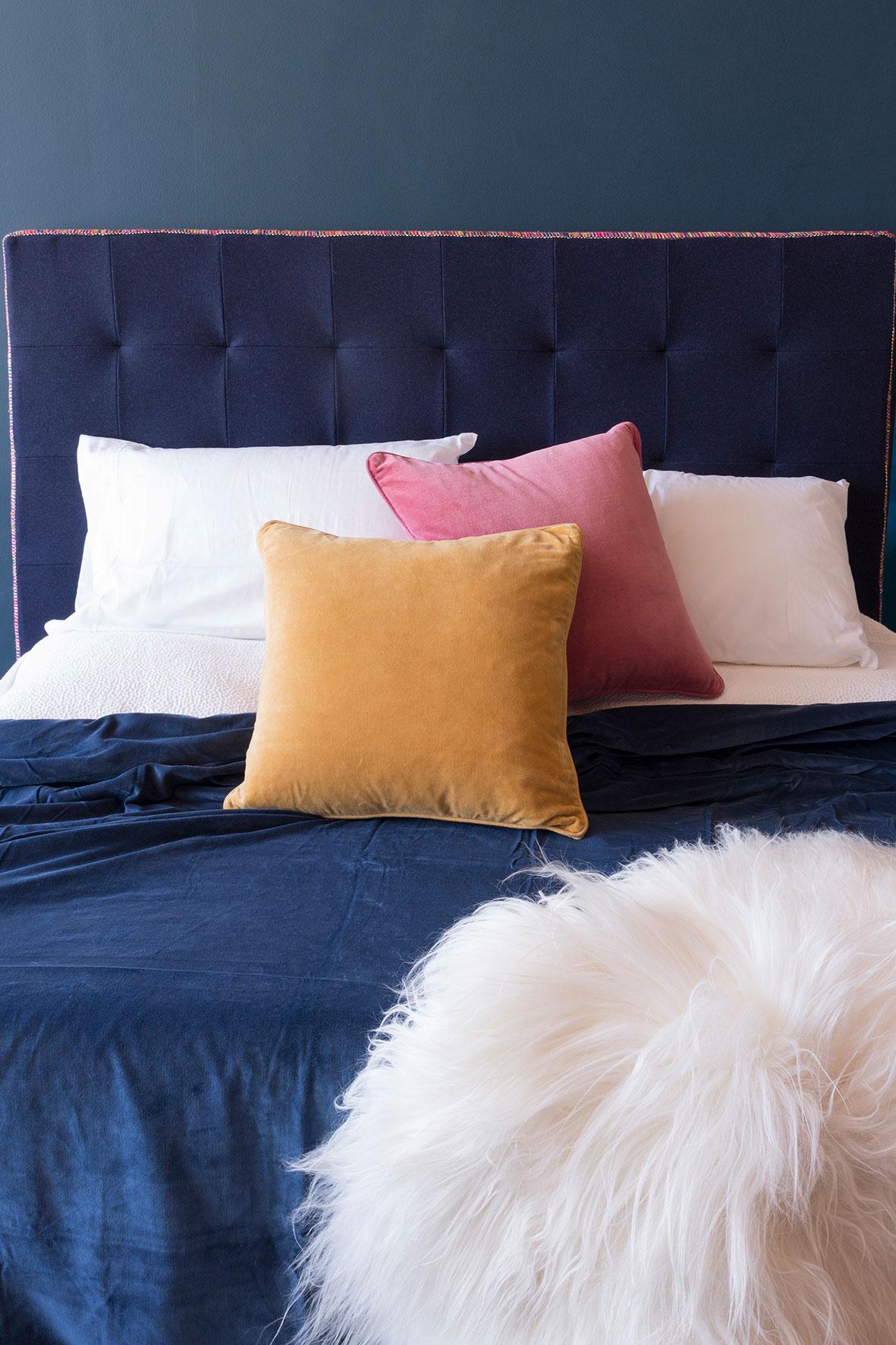 Photographie publicitaire d'un lit avec parure de lit et oreillers colorés.