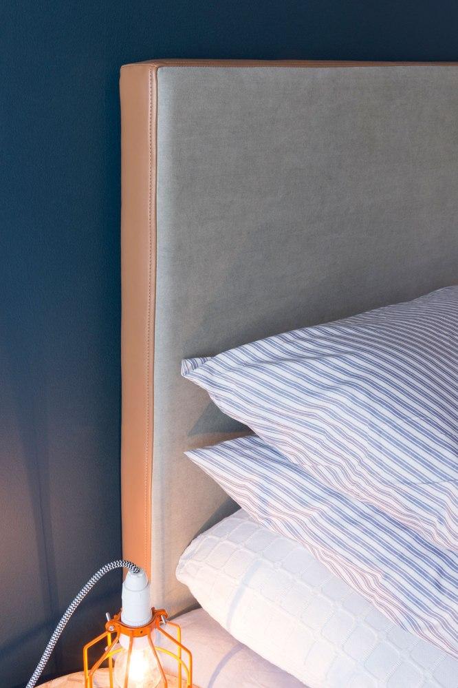 Photographie publicitaire, détail d'une tête de lit avec linge de maison.
