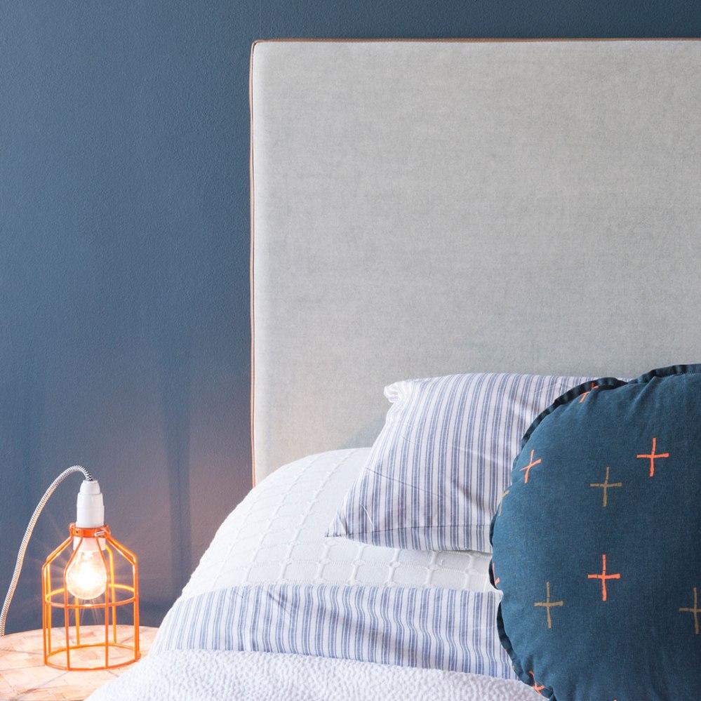 Photographie publicitaire d'une tête de lit avec linge de maison.