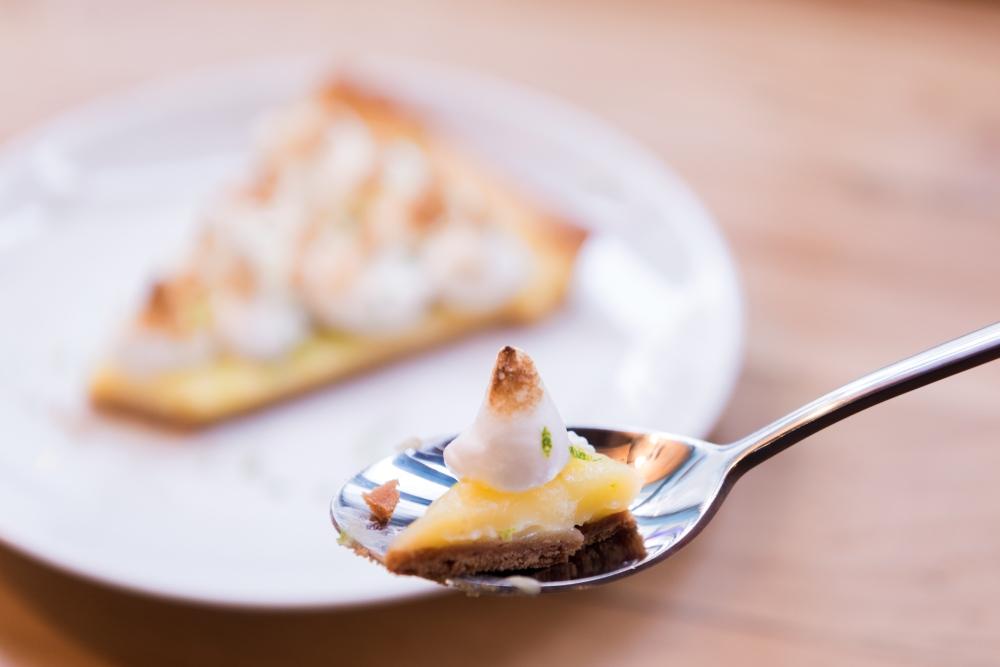 Gros plan sur une cuillère de tarte au citron meringuée.