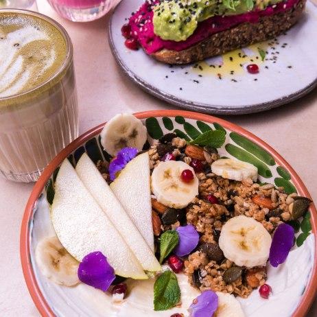 Granola bio avec fruits frais, yaourt grec et fleurs comestibles.