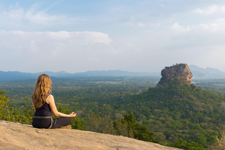 Photo d'une femme de dos, assise en tailleur face au rocher du lion à Sigiriya au Sri Lanka.