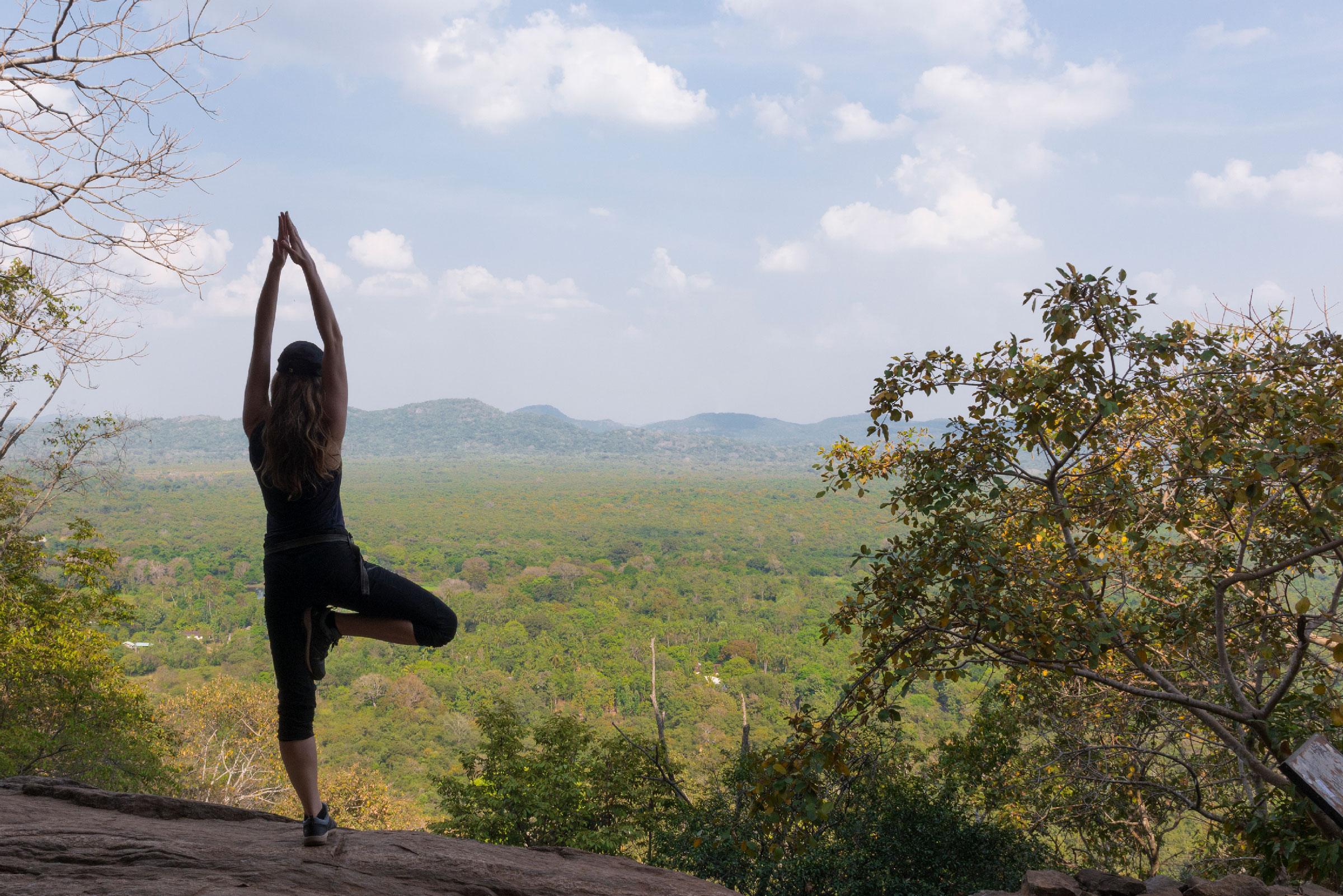 Photographie d'une femme en posture de l'arbre surplombant une forêt.