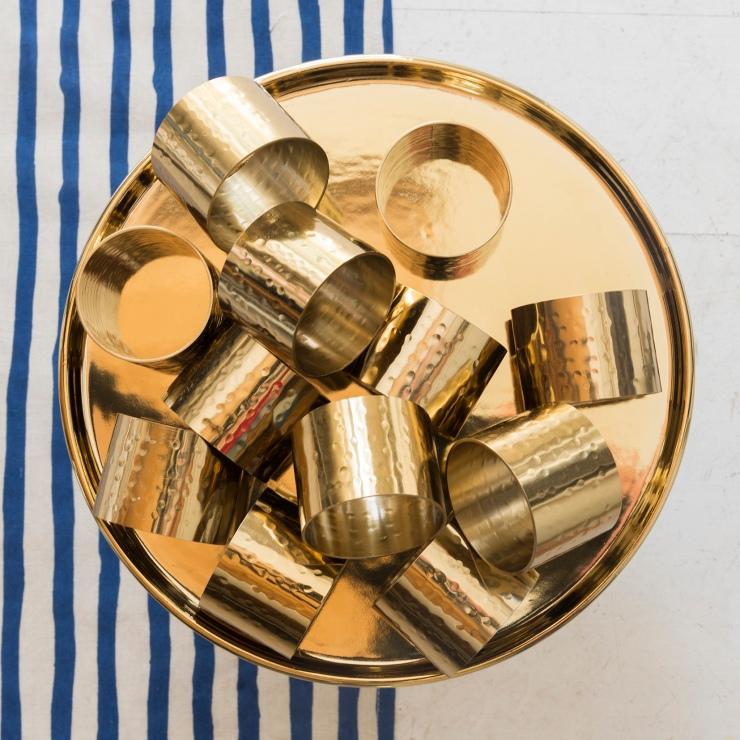 Photographie du dessus d'un plat avec des ronds de serviette dorés.