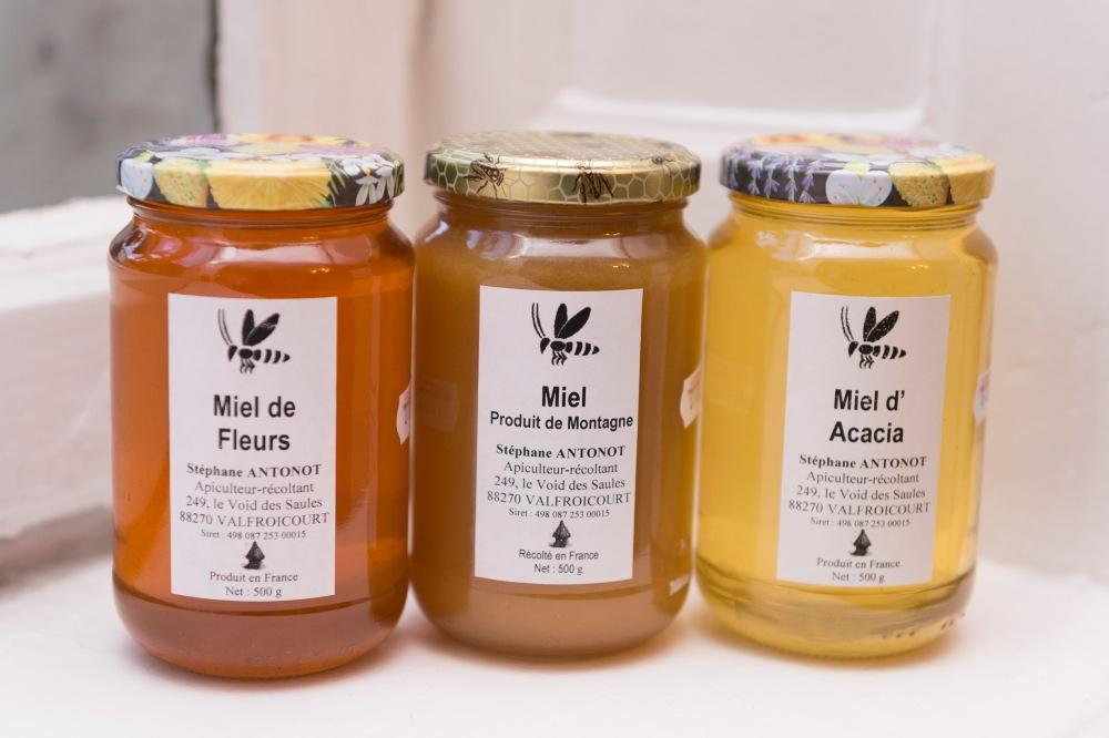 Photographie de face de 3 pots de miels différents.