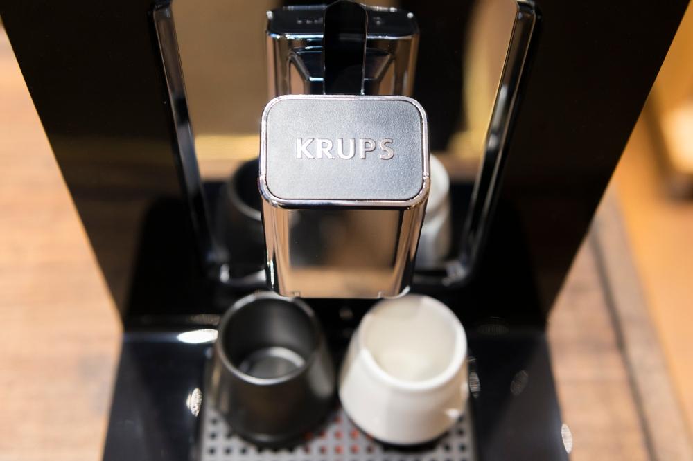 Photographie en gros plan d'une partie d'une machine à café automatique Krups.