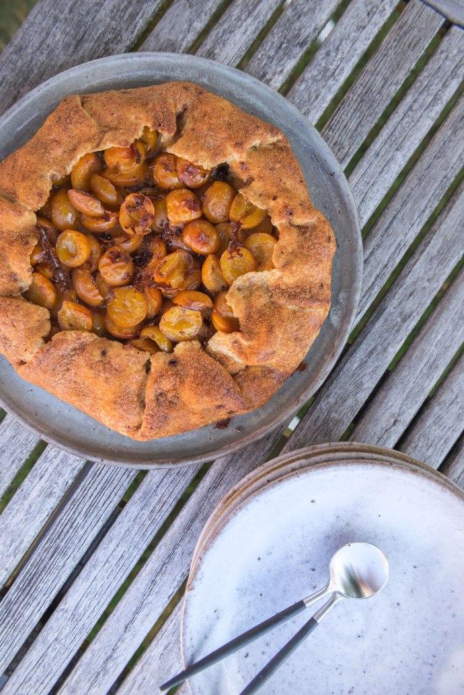 Vue du dessus d'une tarte rustique aux mirabelles et une pile d'assiette.