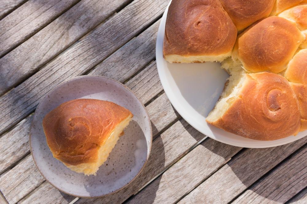 Photo d'une brioche ronde vue du dessus avec une part coupée dans une assiette.