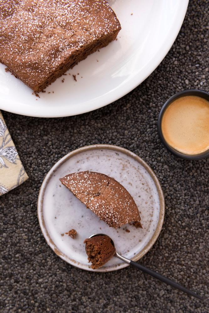 Photo vue du dessus d'un gateau au chocolat dans une assiette blanche avec une part dans une petite assiette grise et une tasse d'espresso.