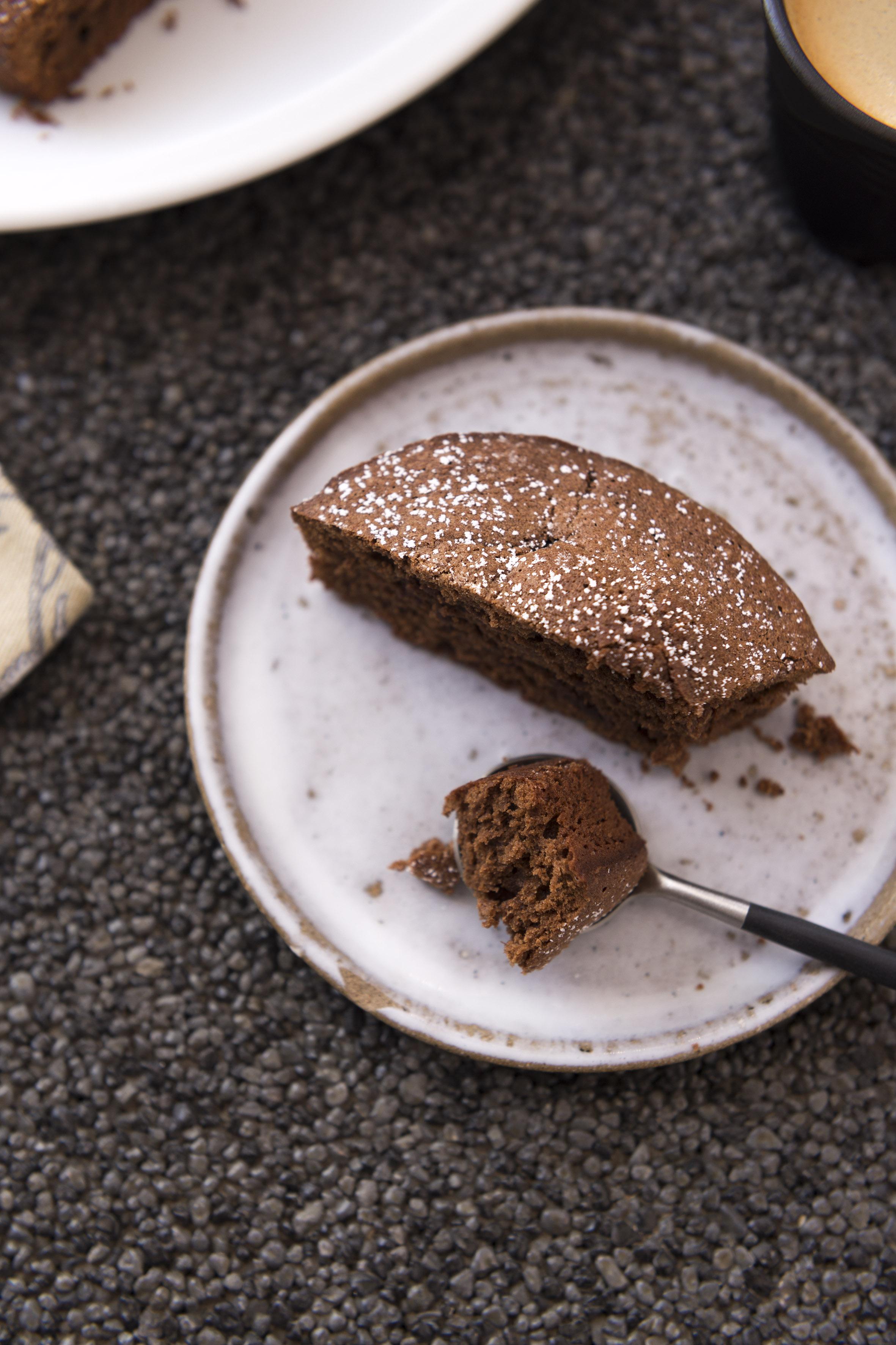 Photo vue de trois quart en gros plan d'une part de gâteau au chocolat avec un morceau dans une cuillère